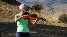 Violinist. Young Woman playing the violin in nature stock video
