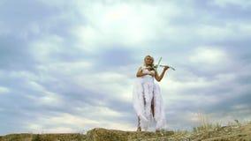Violinista bonito In um vestido branco filme