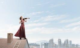 Violinista de la mujer en el vestido rojo que juega melodía contra el cielo nublado Técnicas mixtas foto de archivo