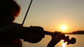 Violinista de sexo femenino que toca el violín en el lago en la puesta del sol metrajes