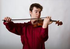 Violinista de sexo masculino adolescente del virtuoso en rojo Imagen de archivo libre de regalías
