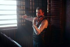Violinista de sexo masculino que juega en el violín contra ventana Imágenes de archivo libres de regalías