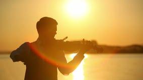 Violinista de sexo masculino que toca el violín en el lago en la puesta del sol almacen de video