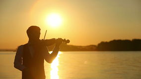 Violinista de sexo masculino que toca el violín en el lago en la puesta del sol almacen de metraje de vídeo
