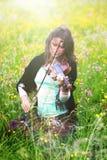 Violinista en un prado por completo de las flores, chica joven que toca el instrumento de música Fotografía de archivo libre de regalías