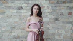 Violinista femminile sicuro nel salto, vestito uguagliante con il violino in mani stock footage