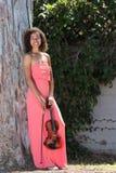 Violinista femminile sorridente in vestito rosa lungo fuori fotografia stock