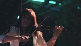 Violinista fresco fresco y expresivo jugando la situación del violín en etapa metrajes