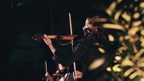 Violinista hermoso de la muchacha en ropa negra y el pelo rizado largo que tocan el viol?n en etapa M?sico fresco de la muchacha  metrajes