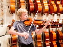 Violinista Playing do menino um violino em Music Store Fotos de Stock