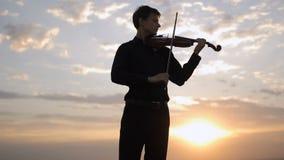 Violinista que juega en la puesta del sol en el tejado Música, arte metrajes