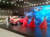 Violinistas em vestidos vermelhos Salão de beleza internacional 2018 do automóvel de Moscou imagem de stock