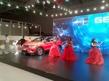 Violinistas em vestidos vermelhos Salão de beleza internacional 2018 do automóvel de Moscou Fotografia de Stock Royalty Free