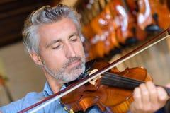 Violinisten som ut försöker fiolen i musik, shoppar Fotografering för Bildbyråer