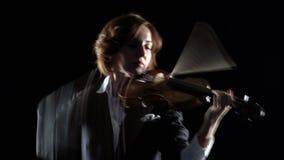 Violinisten utför en fiol i en svart studio Svart bakgrund arkivfilmer