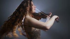 Violinistfrau mit dem langen Haar dreht sich herum und spielt auf Geige auf Hintergrund von Blitzen und von Rauche stock video