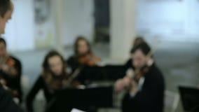 Violinisti e conduttore che giocano musica archivi video