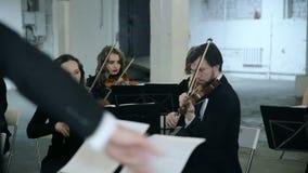 Violinisti e conduttore che giocano musica stock footage