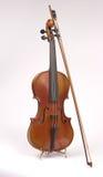 Violino antico sul basamento con l'arco Fotografia Stock Libera da Diritti