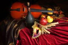 Violino ao lado de uma garrafa do vinho velho e de frutos maduros na tabela, toalha de mesa vermelha de veludo, máscara teatral,  Foto de Stock