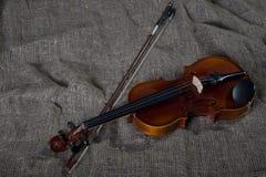 Violino, archetto e cravatta a farfalla, fondo della tela fotografia stock