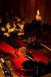 Violino, candela bruciante e foglie di autunno sulla tavola Immagini Stock