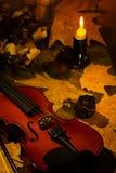 Violino, candela bruciante e foglie di autunno sulla tavola Fotografia Stock