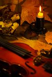 Violino, candela bruciante e foglie di autunno sulla tavola Fotografia Stock Libera da Diritti