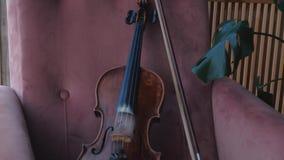 Violino com a cadeira de encontro da curva na sala perto da janela Tiro constante da came vídeos de arquivo