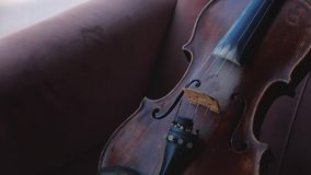 Violino com a cadeira de encontro da curva na sala perto da janela Tiro constante da came filme