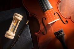 Violino de madeira com ampulheta, pena e livro Foto de Stock