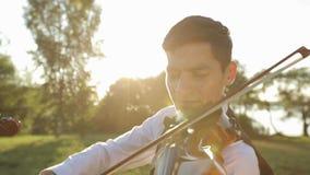 Violino del gioco dell'uomo del violinista sulla natura al tramonto stock footage