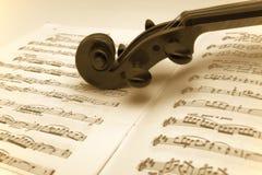 Violino do vintage que descansa em uma música de folha fotografia de stock