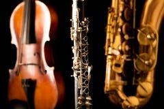 Violino e clarinete do saxofone do conteúdo do saxofone da música no preto Fotografia de Stock Royalty Free