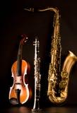 Violino e clarinetto del sassofono tenore del sax di musica nel nero Immagini Stock
