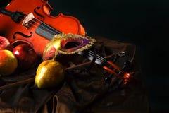 Violino e maschera teatrale sul tessuto accanto a frutta succosa, natura morta olandese Immagine Stock Libera da Diritti