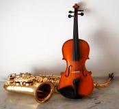 Violino e saxofone em uma tabela de mármore Fotografia de Stock Royalty Free