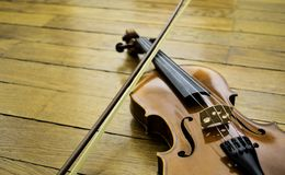 Violino ed arco che riposano sul pavimento di legno immagini stock
