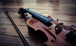 Violino ed arco che riposano sul pavimento di legno in ombra immagine stock