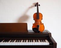 Violino que inclina-se em um piano digital Imagem de Stock Royalty Free