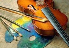 Violino, spazzole e tavolozza su un fondo di legno immagine stock