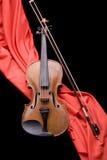Violino sul color scarlatto della seta Fotografia Stock Libera da Diritti