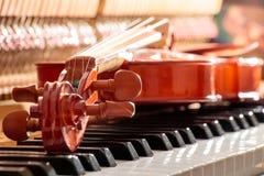 Violino sulle chiavi del piano con la luce posteriore del sole Fotografie Stock