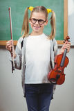 Violino sveglio della tenuta dell'allievo in un'aula Immagini Stock