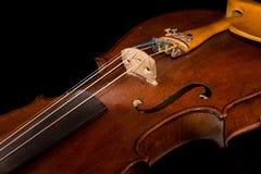 Violino velho no fundo preto Fotografia de Stock Royalty Free