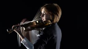 Violist een muzikale samenstelling op een viool in een zwarte studio Zwarte achtergrond stock videobeelden