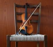 Violon avec l'arc sur une chaise avec un siège de paille Fond en bois de mur Images libres de droits
