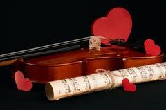 Violon, notes de musique et coeurs rouges Images stock