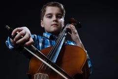 Violoncelista joven que juega música clásica en el violoncelo Imagenes de archivo