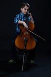 Violoncelista joven que juega música clásica en el violoncelo Fotografía de archivo